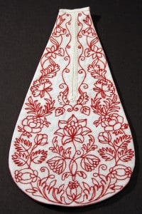 Embroidered pocket in red to match the original.